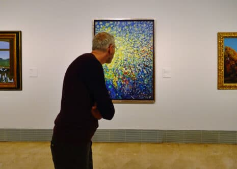 """MADRID, SPAIN - MARCH 26, 2018: man looks at the picture """"Thirty-three Little Girls set out for the White Butterfly Hunt"""", 1958 by Max Ernst in the museum Thyssen-Bornemisza."""